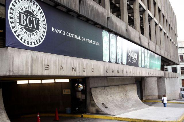 """AME9913. CARACAS (VENEZUELA), 07/05/2019.- Fotografía del 06 de mayo de 2019, de una mujer que camina frente a la sede del Banco Central de Venezuela en Caracas (Venezuela). El Banco Central de Venezuela (BCV) autorizó a las entidades financieras del país a realizar la compra y venta de divisas entre personas naturales y jurídicas a través de mesas de cambio, en la que los interesados podrán presentar cotizaciones de oferta o demanda """"sin restricción alguna"""".EFE/Raúl Martínez"""