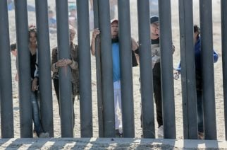 """(FILES) In this file photo taken on November 18, 2018, Honduran caravan members look through through the fence at the US-Mexico border wall at Friendship park in San Ysidro, California. - US President Donald Trump on January 9, 2020, welcomed a court decision that allows $3.6 billion in military funds to be used to build his signature wall on the US-Mexico border. """"Entire Wall is under construction or getting ready to start!"""" the president tweeted following the ruling by the Fifth US Circuit Court of Appeals. (Photo by Sandy Huffaker / AFP)"""