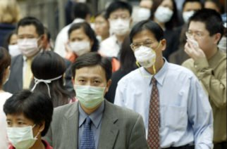 People wear masks on the street to protect against a deadly pneumonia virus in Hong Kong, 31 March 2003.  The death toll in Hong Kong to the disease known as severe acute respiratory syndrome (SARS) is now 15 with 610 people infected with the toll expected to rise.  AFP PHOTO/Peter PARKS        (Photo credit should read PETER PARKS/AFP/GettyImages)